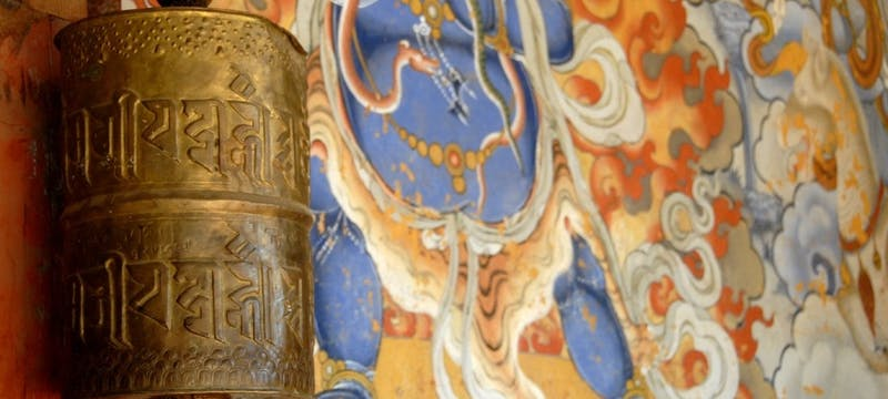 Prayer wheel and painted walls of a colourful monastery